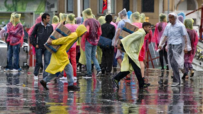 Men carry boxes during heavy rainfall in Taksim square, Friday, June 14, 2013. A meeting between Prime Minister Recep Tayyip Erdogan and representatives of anti-government protesters ended early Friday without a clear resolution on how to end the occupation of a central Istanbul park that has become a flashpoint for the largest political crisis of his 10-year rule. (AP Photo/Vadim Ghirda)