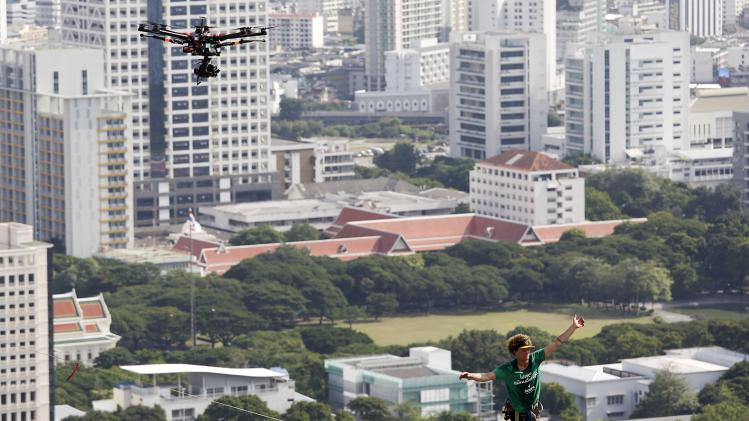 "A drone camera films Andy Lewis of the USA, also known as ""Mr. Slackline"" as he walks on the thin slackline between buildings in central Bangkok"
