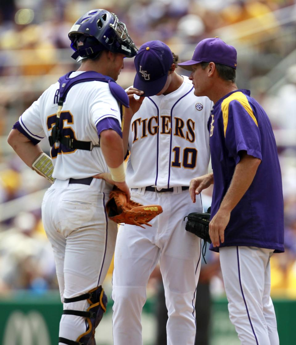 LSU pitching coach Alan Dunn, right, and catcher Ty Ross (26) talk with pitcher Aaron Nola (10) in the first inning of an NCAA college baseball tournament super regional game against Stony Brook in Baton Rouge, La., Friday, June 8, 2012. (AP Photo/Gerald Herbert)