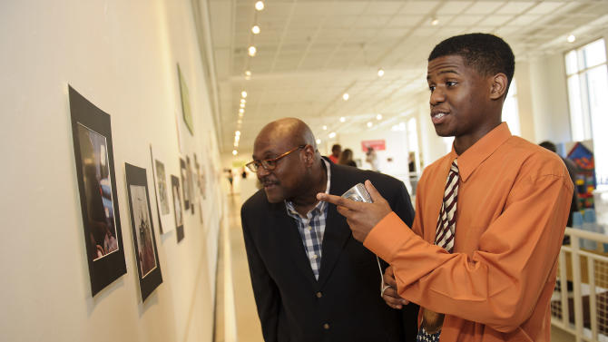 IMAGE DISTRIBUTED FOR BOYS & GIRLS CLUBS OF AMERICA - In this image released on Friday, June 14, 2013, Boys & Girls Clubs of North Alabama Director Edwin Lightbourne and Member Zach M., one of the national winners from the ImageMakers National Photography Contest, look at winning photographs during the ImageMakers Winners' Exhibit Opening at the Youth Art Connection gallery in Atlanta. The Exhibit features more than 120 national and regional award-winning pieces from the ImageMakers National Photography Contest, which is sponsored by Sony Electronics Inc. The ImageMakers National Photography Contest invites Boys & Girls Club youth age 6-18 to explore their creativity and discover photography as a means for self-expression. (Paul Abell/AP Images for Boys & Girls Clubs of America)