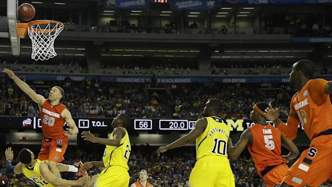 Syracuse's Brandon Triche (20) charges into Michigan's Jordan Morgan (52) during the second half of the NCAA Final Four tournament college basketball semifinal game Saturday, April 6, 2013, in Atlanta. Triche was called for charging.(AP Photo/David J. Phillip)