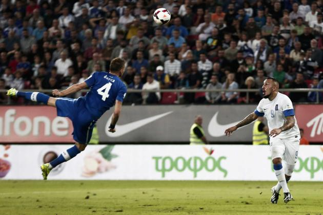 Slovakia's Durica jumps for the ball as Greece's Mitroglou looks on during their 2014 World Cup qualifying soccer match in Athens