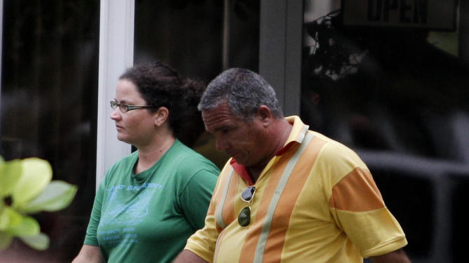 Sharyn Hakken is escorted by a state security officer at the Hemingway Marina in Havana, Cuba, Tuesday, April 9, 2013. Sharyn and her husband Joshua Michael Hakken, who had lost custody of their two young boys, allegedly kidnapped them from Sharyn's parents in Florida and fled by boat to Havana. A foreign ministry official told The Associated Press in a written statement Tuesday that Cuba had informed U.S. authorities of the country's decision to turn over Hakken, his wife and their two young boys. She did not say when the handover would occur. (AP Photo/Franklin Reyes)