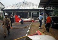 Indonesian rescuers extinguish the fire from a Cessna 202 plane which crashed in Bandung. The light aircraft burst into flames after hitting a building during an air show in Indonesia, killing both the pilots, the transport ministry said