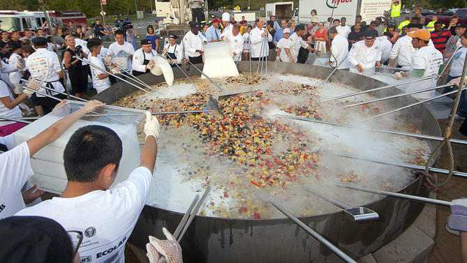 This Monday, Sept. 3, 2012 photo released by the University of Massachusetts in Amherst, Mass., shows a seafood stew cooking at a Labor Day barbecue to celebrate the return of students to the campus. Chefs at the university set a new Guinness World Record by cooking the 6,656-pound seafood stew in the same custom-built, 1-ton, 14-foot frying pan used last year to set a Guinness Record of 4,010 pounds for the world's largest stir-fry.  (AP Photo/University of Massachusetts Amherst, John Solem)