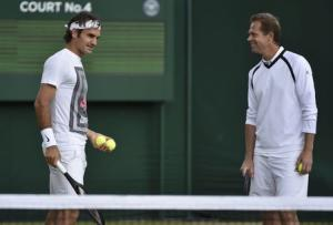 Roger Federer of Switzerland speaks with his coach Stefan Edberg during a practice session at the Wimbledon Tennis Championships in London