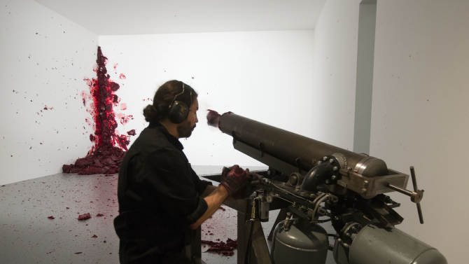 A man performs the art work 'Shooting Into The Corner'  by Indian Artist Anish Kapoor in the exhibition 'Kapoor In Berlin' at the Martin-Gropius-Bau museum in Berlin, Friday, May 17, 2013. The exhibition will run from May 18, until Nov. 24, 2013. (Markus Schreiber)