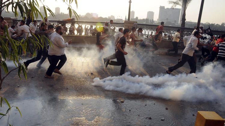 Egyptian protesters run from the site of clashes with security forces, unseen, near the U.S. embassy in Cairo, Egypt, Friday, Sept. 14, 2012, as part of widespread anger across the Muslim world about a film ridiculing Islam's Prophet Muhammad. (AP Photo/Ahmed Gomaa)