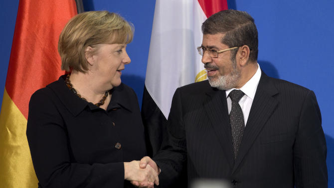 German Chancellor Angela Merkel, left, and President of Egypt Mohammed Morsi, right, shake hands after a joint press conference at the chancellery in Berlin, Germany, Wednesday, Jan. 30, 2013. (AP Photo/Michael Sohn)
