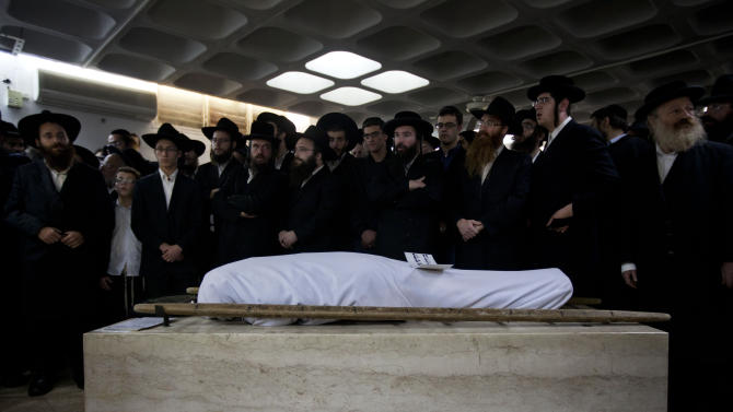 Ultra Orthodox Jewish men gather around the body of Mirah Sharf that was killed in the southern town of Kiryat Malachi by a rocket thought to have been fired by Palestinian militants from the Gaza Strip, during her funeral in Jerusalem, Thursday, Nov. 15, 2012.  Gaza militants led by the ruling Hamas Islamic group showered Israel with rockets Thursday in apparent retaliation for Israel's assassination of Hamas' powerful military chief a day before, and Israel's airforce struck dozens of Hamas-linked targets in Gaza with missiles on Thursday. (AP Photo/Sebastian Scheiner)