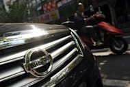 A motorcyclist passes a Nissan car parked on a street in Shanghai in September 2012. Japan's top three automakers said Tuesday their sales in China plunged last month, a sign that a bitter territorial spat between Tokyo and Beijing is hitting trade between the economic giants