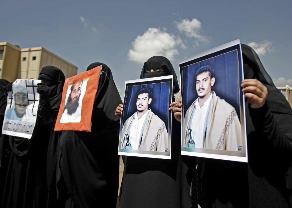 Yemeni women hold photos of their relatives detained in Guantanamo Bay prison during a demonstration in front of the U.S. embassy demanding their release, in Sanaa, Yemen, Monday, April 1, 2013. (AP Photo/Hani Mohammed)