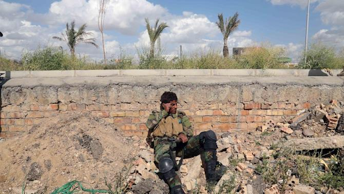 An Iraqi soldier rests during clashes with islamic State extremists in Tikrit, 80 miles (130 kilometers) north of Baghdad, Iraq, Tuesday, March 31, 2015. Iraqi forces battled Islamic State militants holed up in downtown Tikrit, going house to house Tuesday in search of snipers and booby traps, and the prime minister announced security forces had reached the city's center. (AP Photo/Khalid Mohammed)