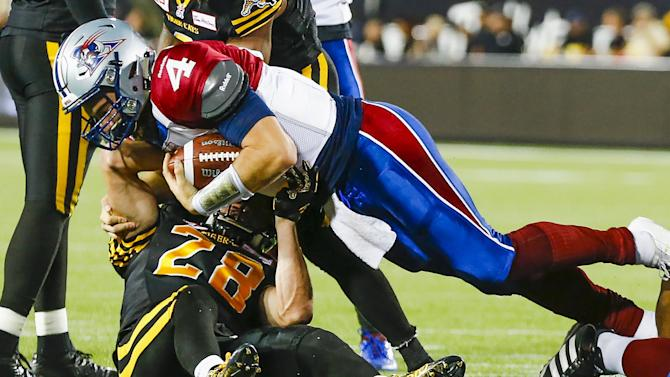 Alouettes quarterback Marsh runs the ball against Hamilton Tiger-Cats' Butler during their CFL football game in Hamilton