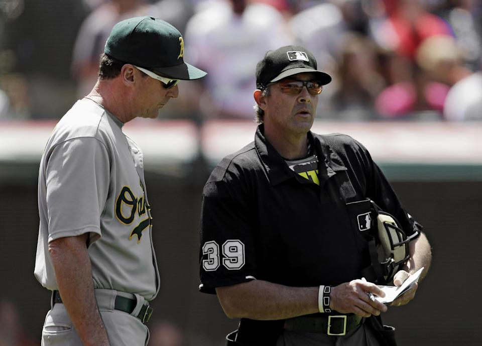 Oakland Athletics manager Bob Melvin goes over a lineup change with home plate umpire Paul Nauert (39) in the seventh inning of a baseball game against the Cleveland Indians, Thursday, May 9, 2013, in Cleveland. (AP Photo/Mark Duncan)