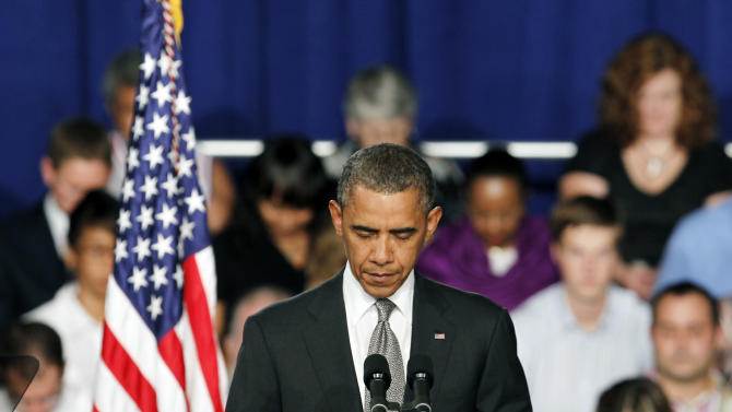 """President Barack Obama takes a moment of silence for the events in Colorado during a campaign stop in Fort Myers, Fla., Friday, July 19, 2012. Obama said the tragic movie theater shooting in Colorado that left 12 people dead is a reminder that life is fragile. He says the event """"reminds us of all the ways that we are united as one American family."""" (AP Photo/Alan Diaz)"""