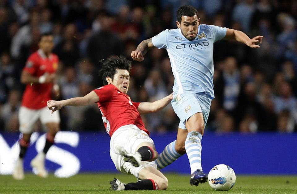 Manchester City's Carlos Tevez, right, fights for the ball against Manchester United's Ji-Sung Park during their English Premier League soccer match at The Etihad Stadium, Manchester, England, Monday, April 30, 2012. (AP Photo/Jon Super)