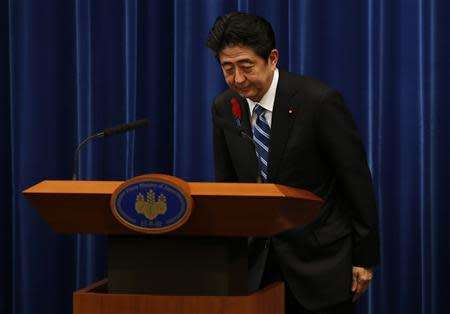 Japan's Prime Minister Shinzo Abe bows at the end of a news conference to announce a raise in the sales tax rate at his official residence in Tokyo
