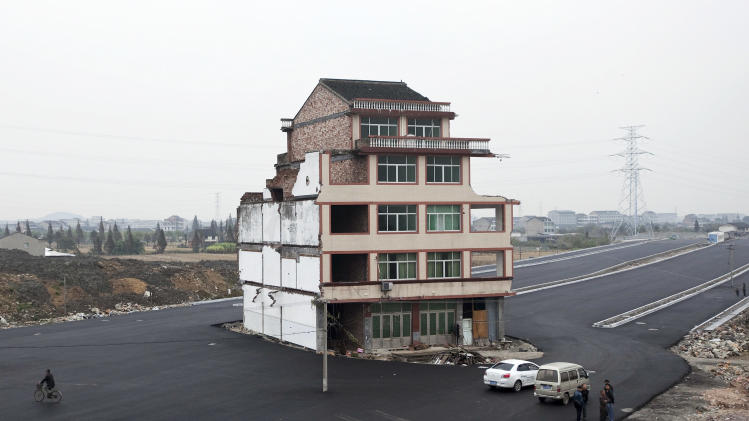 People stand near a house which sits in the middle of a newly built road in Wenling city in east China's Zhejiang province Thursday, Nov. 22, 2012. The house belongs to an elderly man, who refused to sign an agreement to allow his house to be demolished by the authorities, as the compensation offered to him was not enough, according to local media. (AP Photo) CHINA OUT