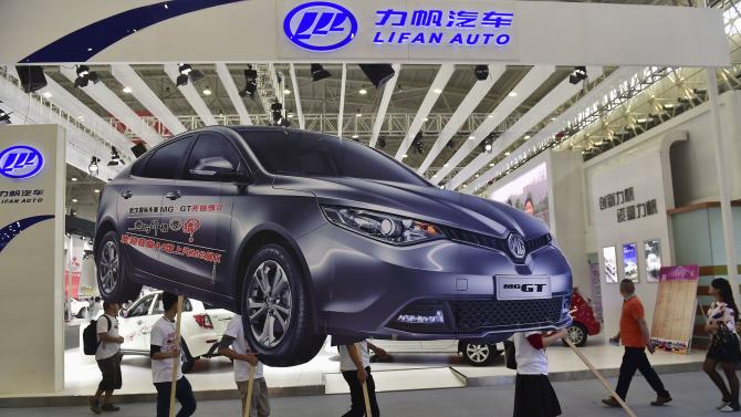 Employees carry an ad for an SAIC Motor car as they walk past a Lifan dislay section during Wuhan 2014 Motor Show