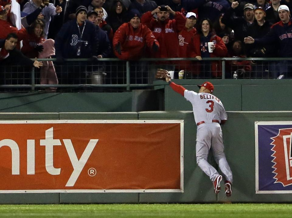 St. Louis Cardinals' Carlos Beltran makes a catch by Boston Red Sox's David Ortiz during the second inning of Game 1 of baseball's World Series Wednesday, Oct. 23, 2013, in Boston. (AP Photo/Matt Slocum)