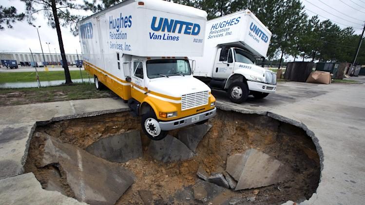 A truck hangs over the edge of a sinkhole that opened up in the parking lot of Hughes Relocation Services, Monday, June 25, 2012, in Salt Springs, Fla. Tropical Storm Debby raked the Tampa Bay area with high wind and heavy rain Monday in a drenching that could top 2 feet over the next few days and trigger widespread flooding. (AP Photo/The Ocala Star-Banner, Alan Youngblood)