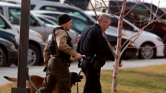 A Natrona County Sheriff's canine handler arrives at the scene of a reported homicide at Casper College on Friday morning, Nov. 30, 2012, in Casper, Wyo. At least one person was killed and another was wounded Friday in an attack at Casper College, a community college in central Wyoming. It happened around 9 a.m., said school spokesman Rich Fujita.  (AP Photo/Casper Star-Tribune, Alan Rogers) MANDATORY CREDIT  TRIB.COM