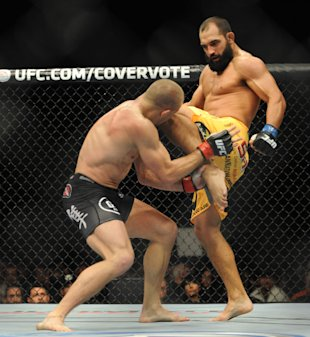 Georges St-Pierre takes a knee to the head from Johny Hendricks. (USA Today)