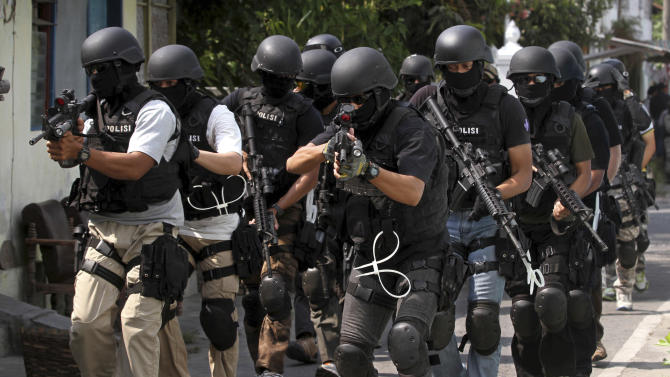 In this Wednesday, Sept. 26, 2012 photo, members of Indonesian police anti-terror unit Special Detachment 88 move into positions as they prepare for a raid in Solo, Central Java, Indonesia. Ten years after terrorist attacks at two Bali nightclubs killed more than 200 people, mostly foreign tourists, Indonesia has won international praise for its counterterrorism efforts. Militant organizations have been fractured and many of their charismatic leaders have been killed or jailed. But an Associated Press analysis shows the number of strikes within the country has actually gone up, especially since 2010, when radical imams called on their followers to focus on domestic targets rather than Westerners. The more recent attacks have been conducted with less expertise, and the vast majority of victims have been Indonesians. (AP Photo)