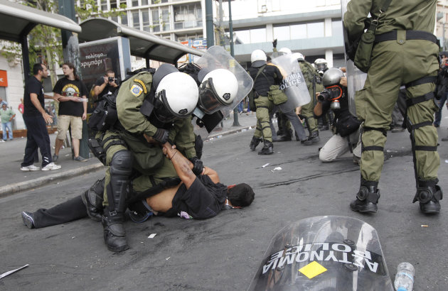 Riot police arrest a demonstrator during clashes in front of the parliament in Athens, Tuesday, Oct. 9, 2012. German Chancellor Angela Merkel got a hostile reception from ordinary Greeks Tuesday when
