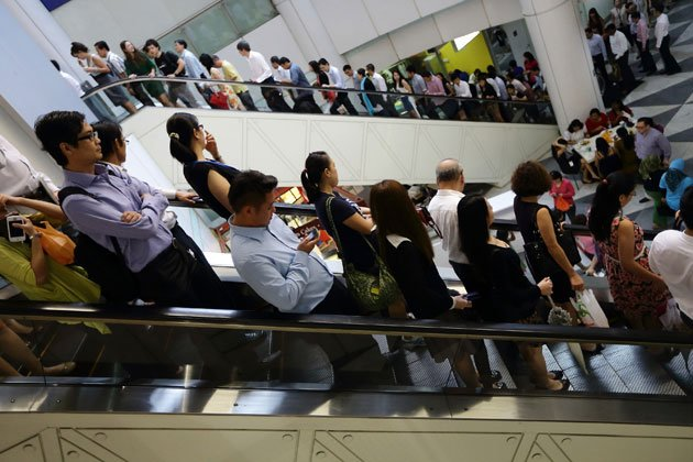 Commuters commute at lunch hour at Raffles Place on February 14, 2013 in Singapore. (Photo by Suhaimi Abdullah/Getty Images)