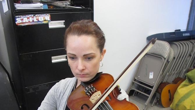 In this Nov. 17, 2012, photo, Sarah Jane Coffman practices the viola with the Hiland Mountain Correctional Facility Orchestra in Eagle River, Alaska. After serving a 14-year sentence for murder, Sarah Jane Coffman, a founding member of the women's string orchestra at the prison in 2003, will debut as a citizen member when the two annual holiday concerts are held Dec. 8, 2012. (AP Photo/Mark Thiessen)