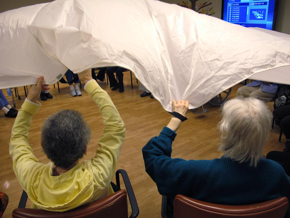 "In this Sept. 20, 2012 photo, dementia patients sitting in a circle formation do an exercise called ""the parachute"" at the Hebrew Home at Riverdale in the Bronx borough of New York. The Hebrew Home has a program that provides care and activity overnight for dementia victims with sleep problems. (AP Photo/Jim Fitzgerald)"