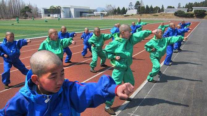 In this Thursday, April 18, 2013 photo, eleven-year-old students who were newly admitted into the Mangyongdae Revolutionary School, in Pyongyang, North Korea practice taekwondo. The school is run by the military and school administrators say it was originally set up in 1947 for children who had lost their parents during Korea's fight for liberation from its Japanese occupiers. (AP Photo)