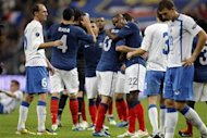 France's Eric Abidal reacts with teammate after drawing with Bosnia to qualify to the Euro 2012 championship at the Stade de France stadium in Saint-Denis