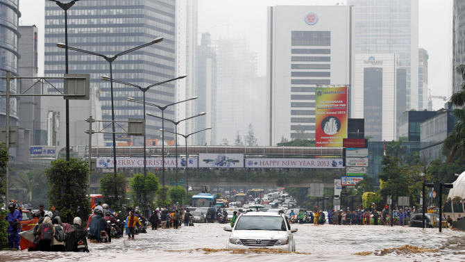 People wade through a flooded main road in Jakarta, Indonesia, Thursday, Jan. 17, 2013. Floods regularly hit parts of Jakarta in the rainy season, but Thursday's inundation following an intense rain storm appeared especially widespread. (AP Photo/Achmad Ibrahim)