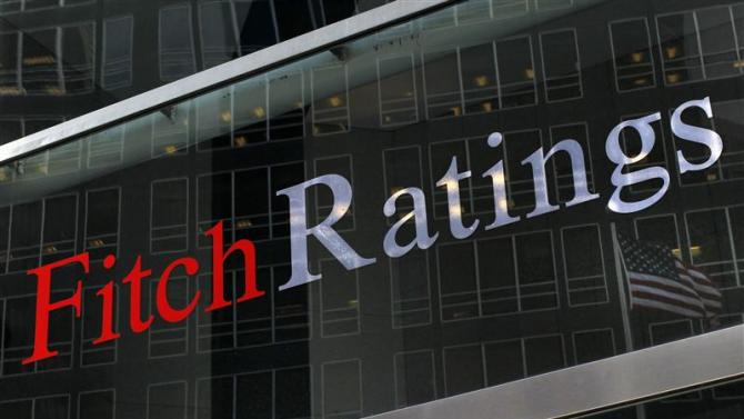 File photo of a flag reflected on the window of the Fitch Ratings headquarters in New York