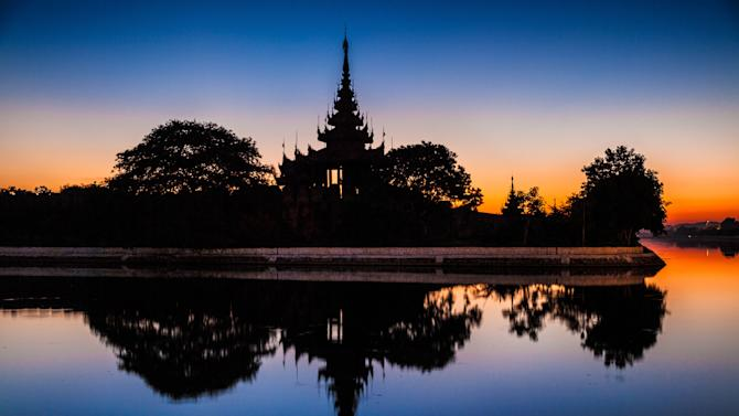 In this December 2012 photo Mandalay Palace is reflected in a surrounding moat, in Mandalay, Myanmar. (AP Photo/Richard Camp)