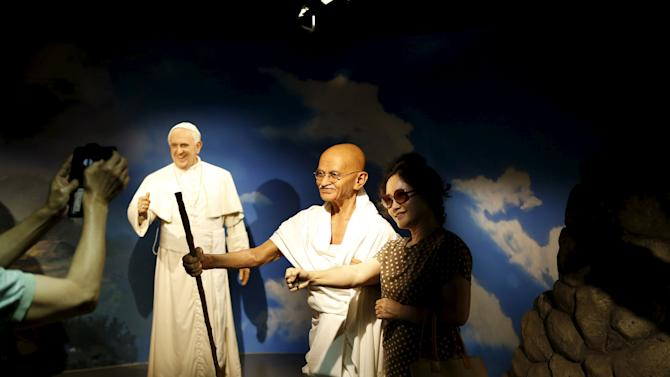 A woman poses for photographs next to the wax figures of Mahatma Gandhi and Pope Francis at Grevin Wax Museum in central Seoul
