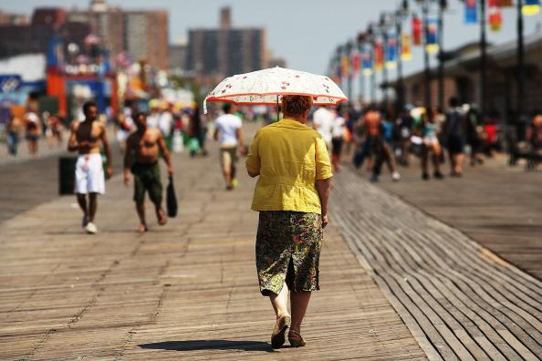 woman walks down the boardwalk in Coney Island on July 12, 2012 in