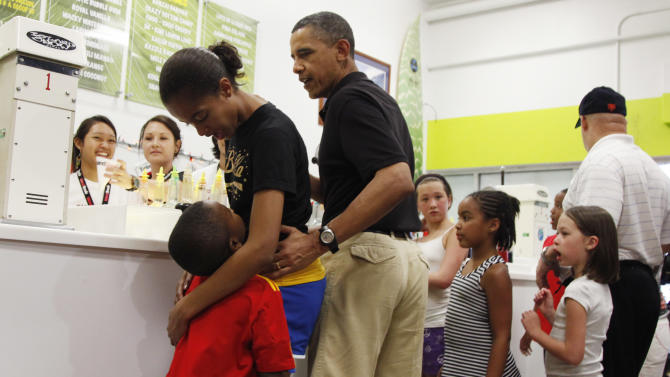 President Barack Obama, third from left, orders shave ice at Island Snow at Kailua Beach Center while on vacation with the first family in Kailua, Hawaii, Monday, Dec. 27, 2010. Second from left is Malia Obama. (AP Photo/Carolyn Kaster)