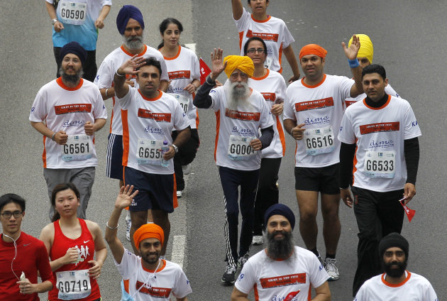 Centenarian marathon runner Fauja Singh, 101, center, originally from Beas Pind, in Jalandhar, India but who now lives in London, runs in a 10-kilometer race, part of the annual Hong Kong Marathon, in