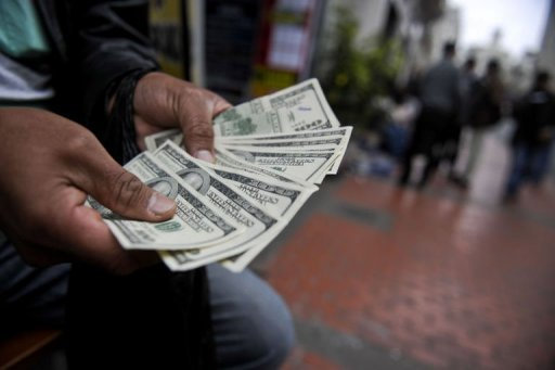 <p>A street money changer counts US 100 dollar bills in Lima on September 6, Peru, one of Latin America's fast-growing economies and a hub of the global cocaine trade, has emerged as a producer of counterfeit US dollars being used both abroad and at home.</p>