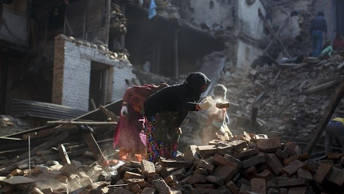 Local residents clear the rubble from their homes which were destroyed after last week's earthquake in Bhaktapur