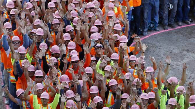 Construction workers and hospital employees wear pink hard hats and form a giant pink ribbon to promote the start of  Breast Cancer Awareness Month in La Jolla