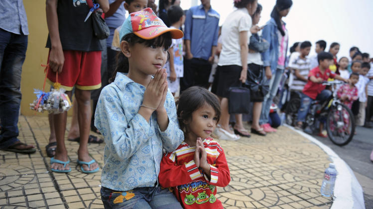 Two girls pray outside the gate of the Royal Palace in Phnom Penh, Cambodia, after the death of former King Norodom Sihanouk, Monday, Oct. 15, 2012. Sihanouk died of a heart attack Monday in Beijing, where he had been receiving medical treatment since January for a variety of ailments. He was 89. (AP Photo)