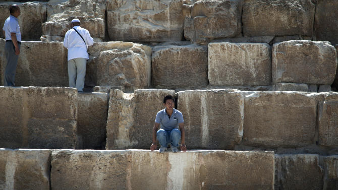 In this Thursday, Sept. 27, 2012 photo, a foreign tourist looks on as he sits during his visit to the historical site of the Giza Pyramids, near Cairo, Egypt. The Egyptian demonstrations against an online film that was produced by a U.S. citizen originally from Egypt and denigrates the Prophet Muhammad were part of a wider explosion of anger in Muslim countries. They happened near the U.S. Embassy, far from the pyramids of Giza on Cairo's outskirts, and a lot further from gated Red Sea resorts, cocoons for the beach-bound vacationer. Yet the online or TV images _ flames, barricades, whooping demonstrators _ are a killjoy for anyone planning a getaway, even though the protests have largely subsided. Tour guides in Egypt say tourist bookings are mostly holding, but they worry about a dropoff early next year, since people tend to plan several months ahead.(AP Photo/Khalil Hamra)
