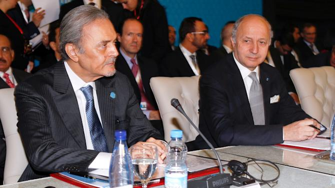 """Saudi Arabia's Foreign Minister, Saud Al Faisal, left, French Foreign Minister Laurent Fabius, right, wait for the start of a meeting of the Friends of the Syrian People in Marrakech, Morocco, Wednesday Dec. 12, 2012. The Syrian opposition called for """"real support"""" and not just recognition on Wednesday, hours after the U.S. declared its new coalition was the """"legitimate representative"""" of its country's people. Bnner behind reads: 4th meeting of the group of """"Friends of the Syrian People"""". (AP Photo/Abdeljalil Bounhar)"""