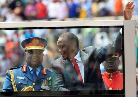 Kenya's President Kenyatta and General Karangi arrive atop a truck with an armoured shield protection glass during celebrations to mark Kenya's Madaraka Day at Nyayo national stadium in Nairobi