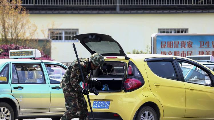 A paramilitary policeman checks the trunk of a car before it enters Kunming railway station in Yunnan